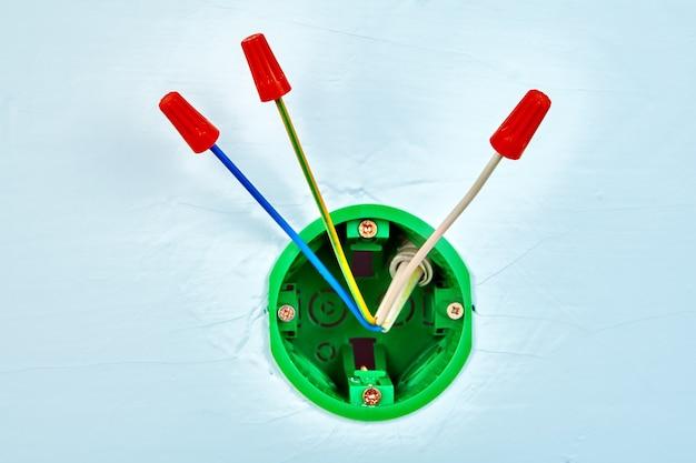 Złącza elektryczne na końcach przewodów miedzianych wewnątrz okrągłej skrzynki elektrycznej do przełącznika.