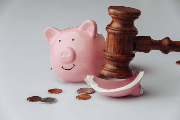 Złamana różowa skarbonka z monetami i drewnianym młotkiem sędziego