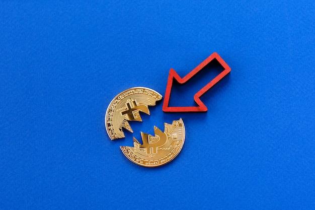 Złamane bitcoin, kryptowaluta spadająca z czerwoną strzałką