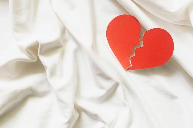 Złamane czerwone serce na białej tkaninie. koncepcja rozwodu.