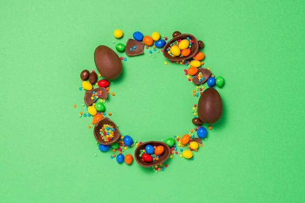 Złamane i całe czekoladowe pisanki, wielobarwne słodycze. krzew. koncepcja obchodów wielkanocy, ozdoby wielkanocne. leżał płasko, widok z góry. kopiuj przestrzeń. kształt koła. wesołych świąt wielkanocnych.