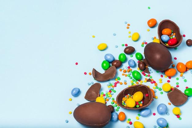 Złamane i całe czekoladowe pisanki, wielobarwne słodycze na niebieskim tle. koncepcja świętowania wielkanocy, ozdób wielkanocnych, poszukiwanie słodyczy dla zajączka. leżał płasko, widok z góry. kopiuj przestrzeń.