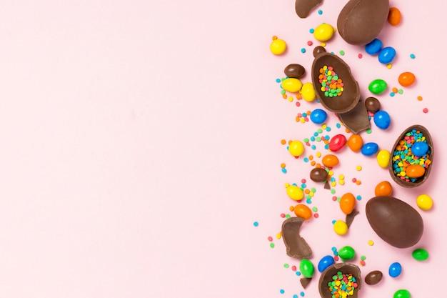 Złamane i całe czekoladowe pisanki, wielokolorowe słodycze, różowe tło. krzew. koncepcja obchodów wielkanocy, ozdoby wielkanocne. leżał płasko, widok z góry. kopiuj przestrzeń. wesołych świąt wielkanocnych.