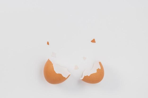 Złamane jajko na białym tle z pękniętą skorupką.