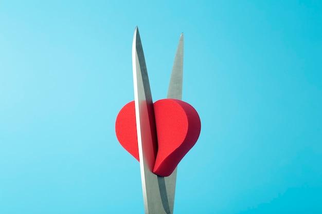 Złamane serce cięte nożyczkami na kolorowym tle. nieszczęśliwa miłość