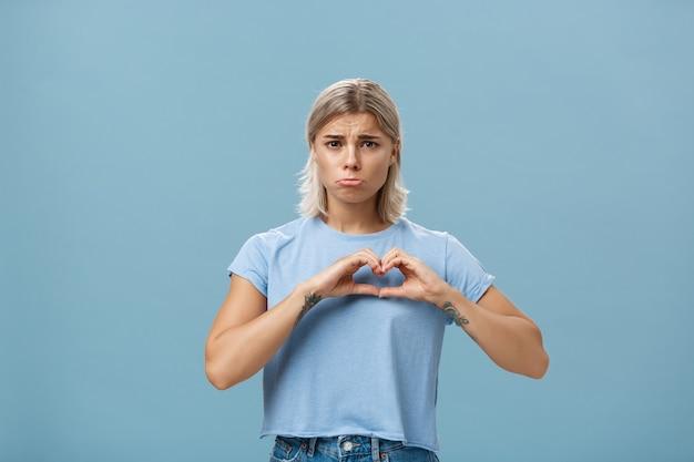 Złamane serce. smutna i ponura dziewczyna ze złamanym sercem, z blond włosami wytatuowanymi na ramionach i opaloną skórą, zaciskająca usta, jęcząca i narzekająca, kochająca się na piersi stojąca nieszczęśliwa w pobliżu niebieskiej ściany