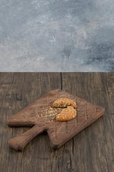 Złamane słodkie ciasteczka owsiane na drewnianej desce do krojenia.