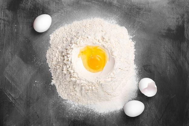 Złamane surowe jajko w kupach mąki pszennej na ciemnej przestrzeni