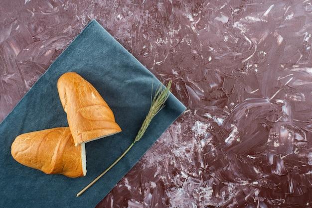 Złamany bochenek białego chleba z kłosem pszenicy na jasnym tle.