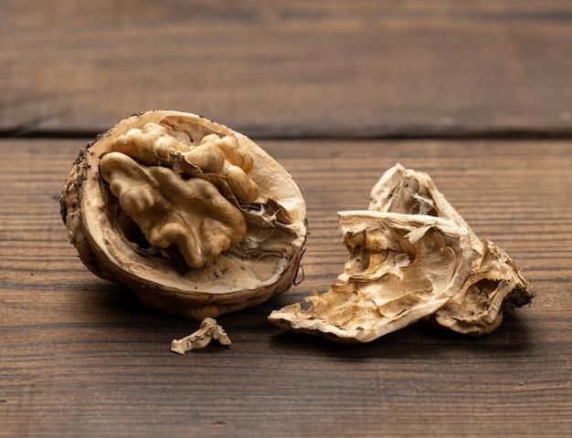 Złamany orzech na brązowym drewnianym stole, z bliska