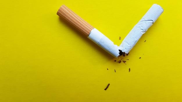 Złamany papieros na białym tle na żółtym tle. widok z góry.