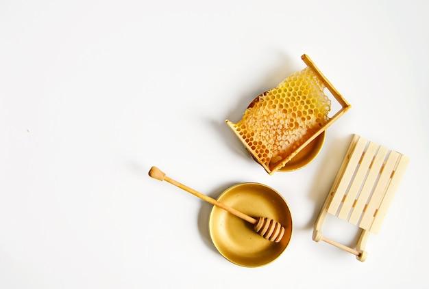 Złamany żółty plaster miodu z miodem na stole obok ozdobnych sań