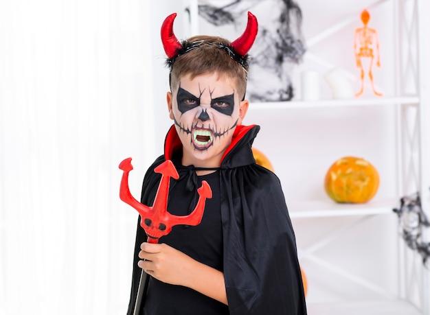 Złe dziecko z pomalowaną twarzą trzymającą trójząb