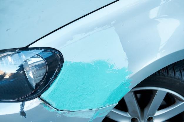 Źle naprawiony błotnik samochodu pokryty kitem