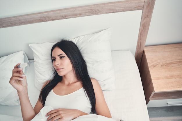 Źle się czuć. poważna brunetka patrzy na ekran, sprawdzając temperaturę i leżąc w łóżku