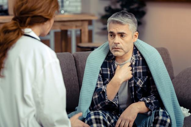 Źle się czuć. przygnębiony chory mężczyzna siedzący naprzeciwko lekarza, czując się chory