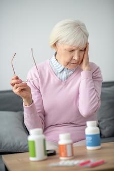 Źle się czuć. starszy kobieta siedzi na kanapie i źle się czuje