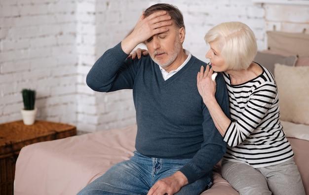 Źle się czuję. starszy chory mężczyzna dotyka czoła, a starsza żona stara się go wspierać.