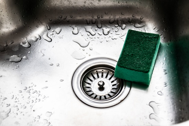 Zlew kuchenny i zielona gąbka do naczyń. krople wody na metalu