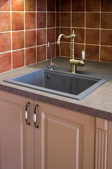Zlew na powierzchni kuchni za pomocą brązowego dźwigu