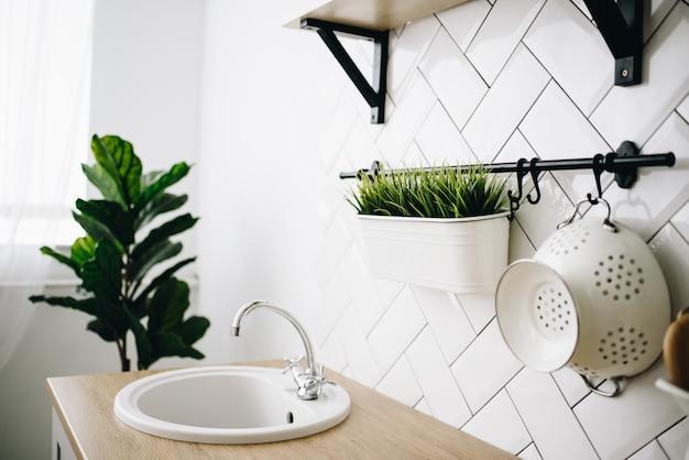 Zlew w przestronnej nowoczesnej skandynawskiej kuchni na poddaszu z białymi kafelkami. jasny pokój. nowoczesne wnętrze.