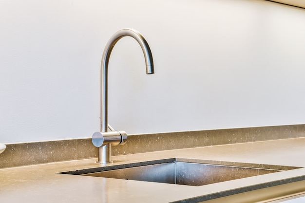 Zlewozmywak z błyszczącym kranem zainstalowany pod nowoczesną ladą przy słoiku z przyprawami i kuchenką gazową w kuchni w domu