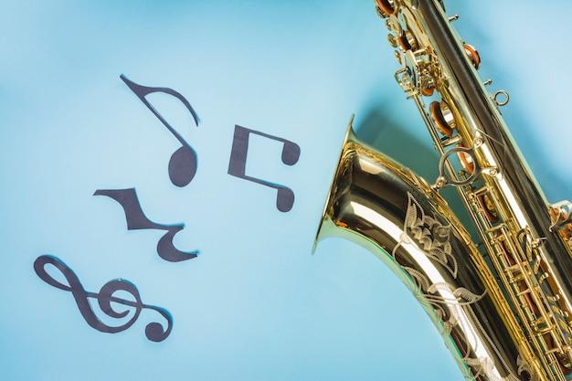 Złoci saksofony z muzykalnymi notatkami na błękitnym tle