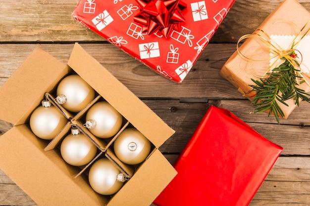 Złoci świąteczni ornamenty w pudełku z bożenarodzeniowymi teraźniejszość