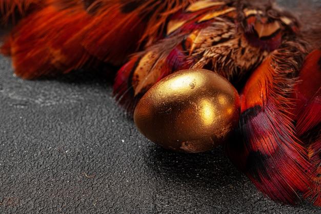 Złoci wielkanocni jajka na czerwonych ptasich piórkach zamykają up