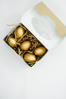 Złoci wielkanocni jajka w pudełku z złotymi gwiazdami na białym tle