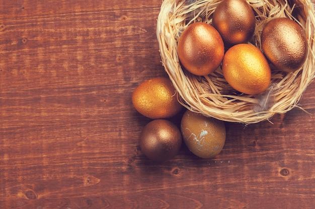 Złociści wielkanocni jajka na drewnianym tle