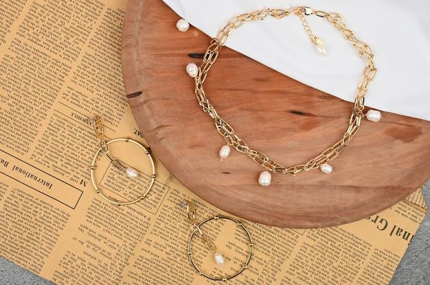 Złocista biżuteria dla kobiet na drewnianym tle