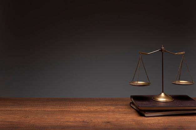 Złocista skala balansu mosiądzu umieszczona na starych książkach i drewnianym stole z szarym tłem