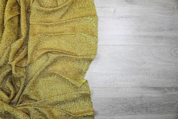 Złocista tkanina na drewnianym tekstury tle
