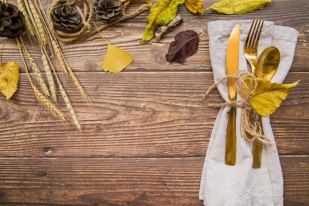 Złocisty cutlery ustawiający na stole z ulotkami