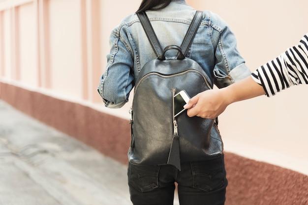 Złodziej kradnący telefon komórkowy z torby podróżnika na ulicy.