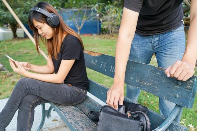 Złodziej próbuje ukraść portfel w torbie podczas gdy kobieta używa telefon komórkowego i słucha t