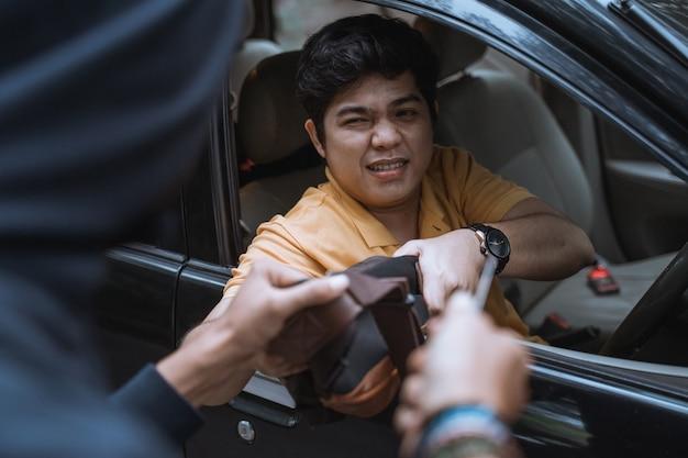 Złodziej próbuje ukraść torbę człowiekowi siedzącemu w samochodzie