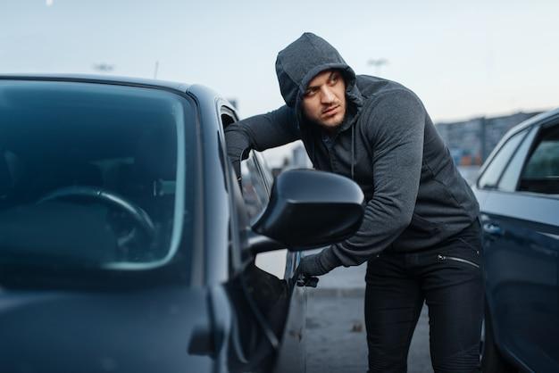 Złodziej samochodów wyważający drzwi, kryminalna praca, włamywacz