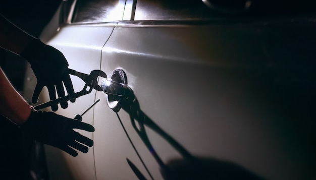 Złodziej samochodów za pomocą narzędzia, aby włamać się do samochodu