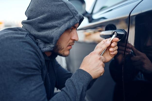Złodziej samochodów ze śrubokrętem łamiącym zamek drzwi. zakapturzony męski złodziej otwierający pojazd na parkingu.