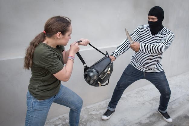 Złodziej trzymający nóż, grabież kobiet, torba scramble