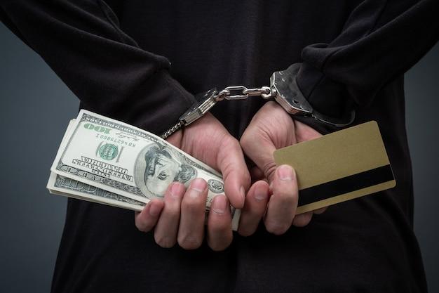 Złodziej w czarnym kapeluszu, zasłaniający twarz, został aresztowany na szaro