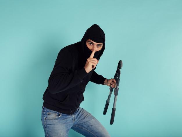 Złodziej w kominiarce w ciszy kradnie mieszkania z przecinakami do drutu w ręku