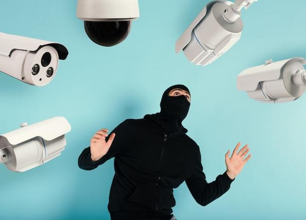 Złodziej w kominiarce został zauważony próbując ukraść mieszkanie z systemu monitoringu z przestraszoną miną
