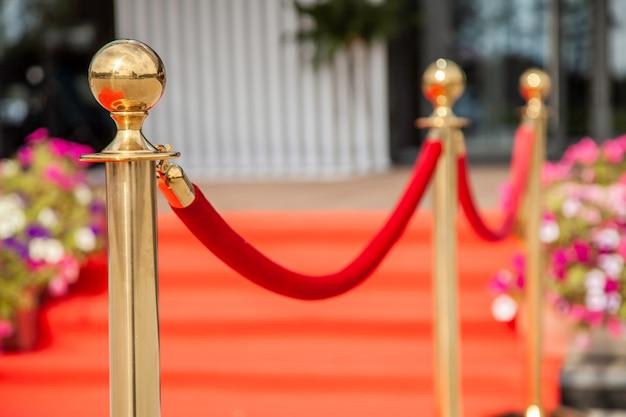 Złota bariera linowa z czerwonym dywanem zdarzeń