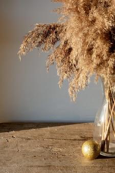 Złota beżowa trawa pampasowa stoi w szklanym wazonie na drewnianej ścianie w promieniach zachodzącego słońca, koncepcja monochromatyczna. naturalne abstrakcyjne ściany i ramy