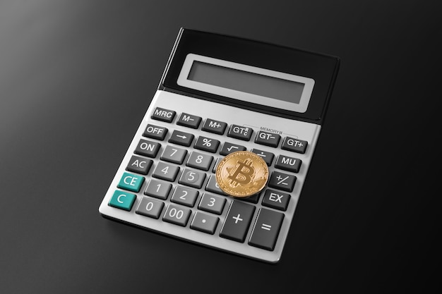 Złota bitcoin moneta na kalkulatora zakończeniu up odizolowywającym na czerni
