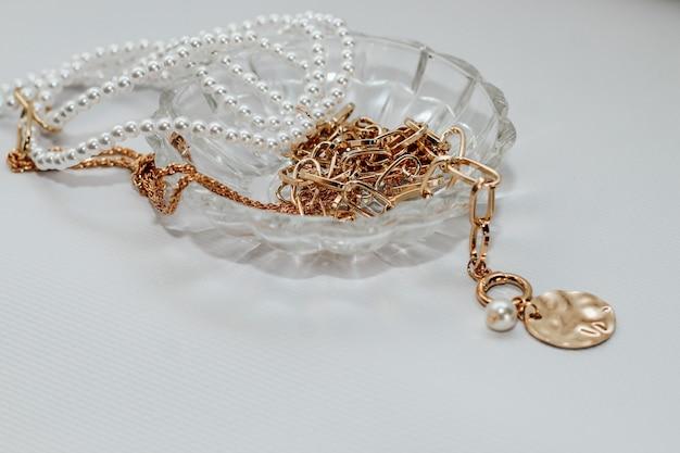 Złota biżuteria, blastety i łańcuszek z koralikami i perłami w kryształowym stojaku na szarym tle. treści biznesowe.