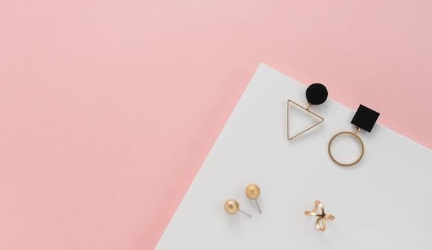 Złota biżuteria na różowym i białym tle